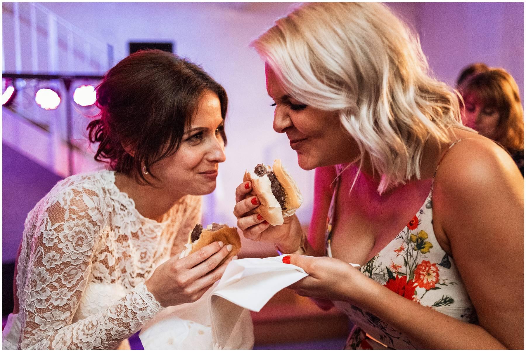 Bride and bridesmaid eating burgers at wedding