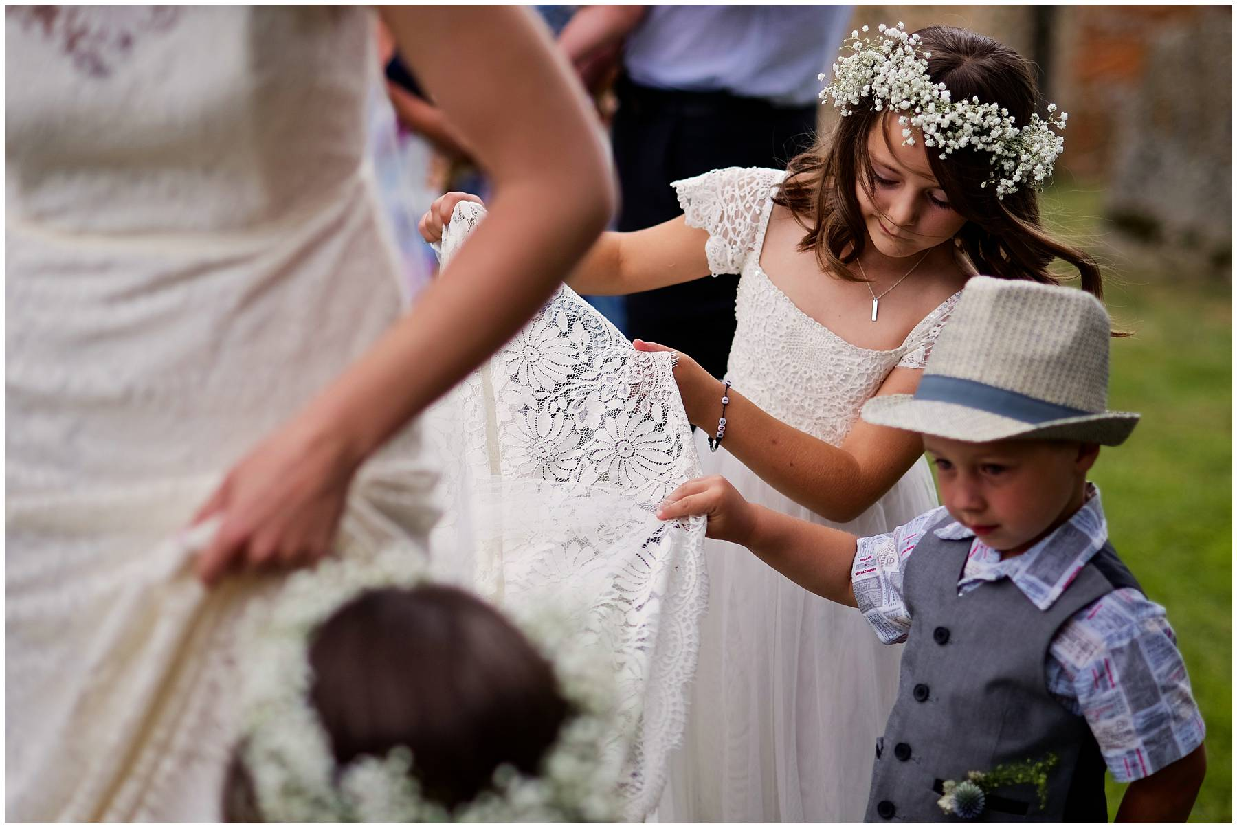 cute kids helping bride with her dress