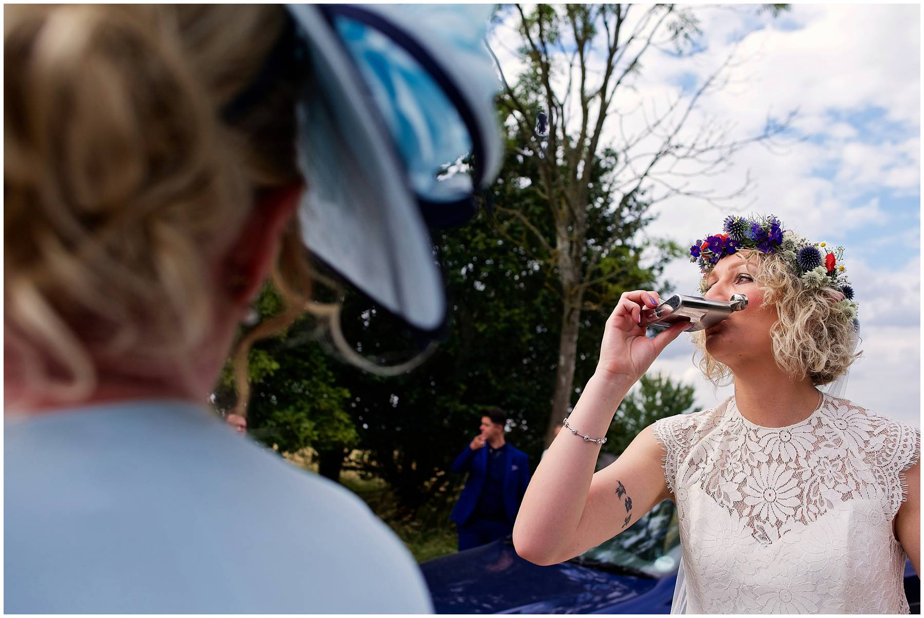 Festival bride drinking from hip flask