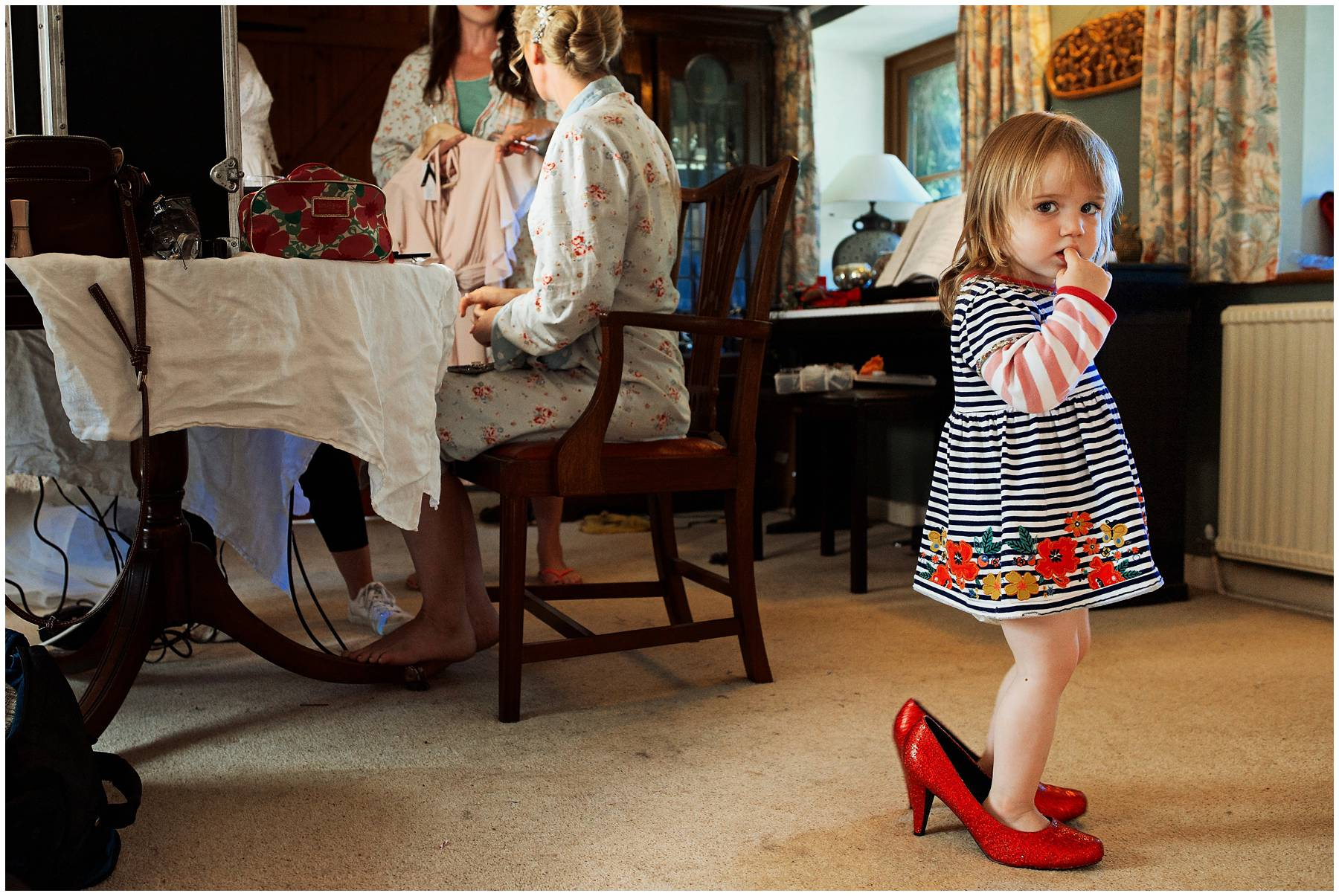 Cute little girl wearing adult red shoes
