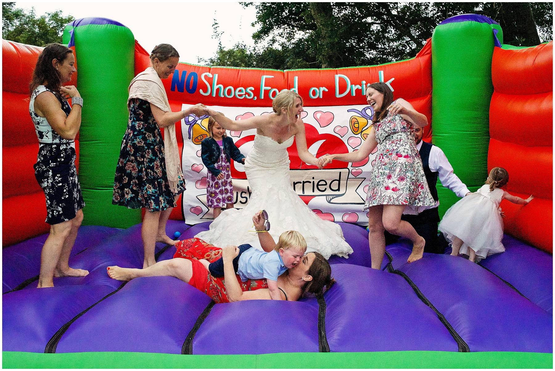 Bride and guests on bouncy castle in Taunton